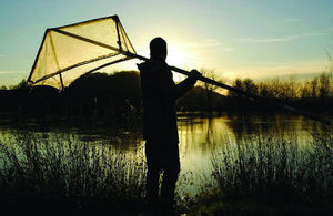 A fisherman with a net suitable for elver fishing standing by a river bank, backlit by the sun