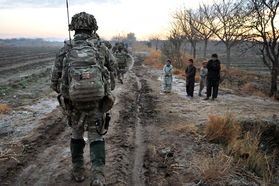 Afghan children watch soldiers on patrol pass by