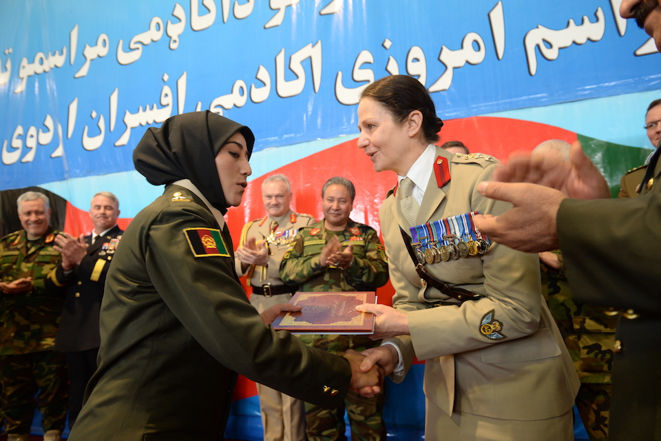 A British officer presents an Afghan cadet with their graduation award