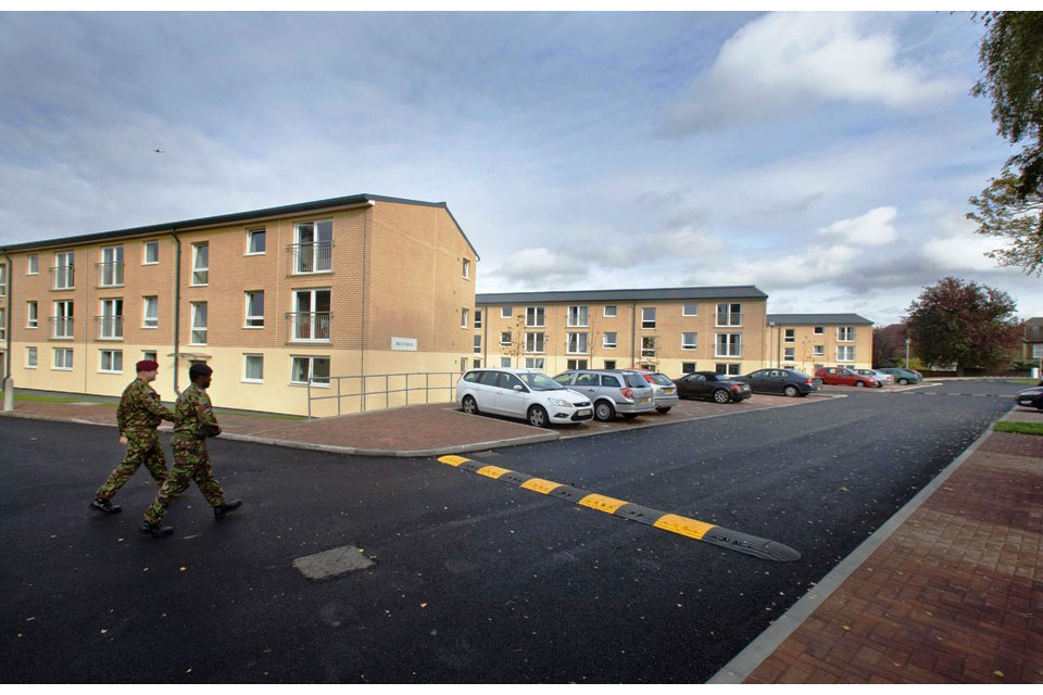 Example of service family accommodation showing 2 military personnel walking past 3 blocks of housing, all of which are 3 storeys high. There is off road car parking and speed bumps.