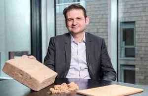 MDF Recovery entrepreneur Craig Bartlett sitting at a desk with an example of waste MDF fibreboard.
