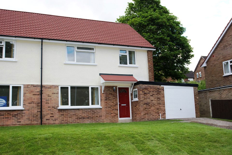 Example image of Service family accommodation shows a modern semi detached house with garage and shared front garden of green lawns.