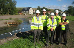 Several members of the Environment Agency next to a river with their arms crossed