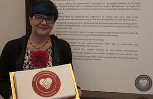 Baroness Neville-Rolfe holding a Women in Finance Charter 1 year anniversary cake