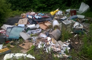 Photograph showing household waste, including a mattress and broken furniture, strewn around a woodland clearing.