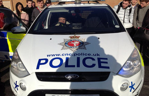 Students at the college look around a CNC police car
