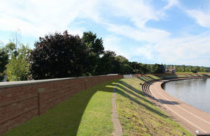 Artist's drawing of a brick wall on top of a small embankment by the edge of water