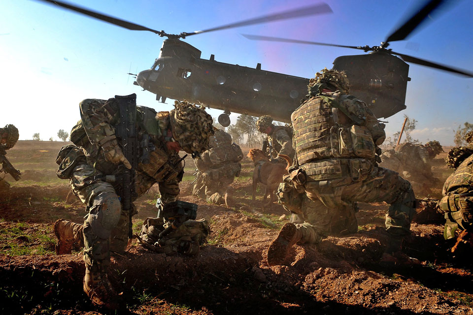 Royal Marines brace themselves against the downdraft from an incoming RAF Chinook helicopter