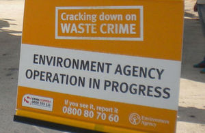 Stock photo of an orange Environment Agency banner which says cracking down on waste crime