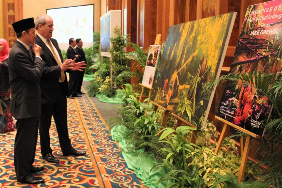 British High Commissioner, David Campbell talking to the Minister of Development about artist Jake Grewall's painting of Brunei's rainforests