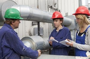 Apprentice engineers being taught on the job