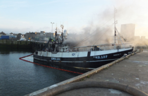 Photograph of fishing vessel Ardent II on fire while alongside