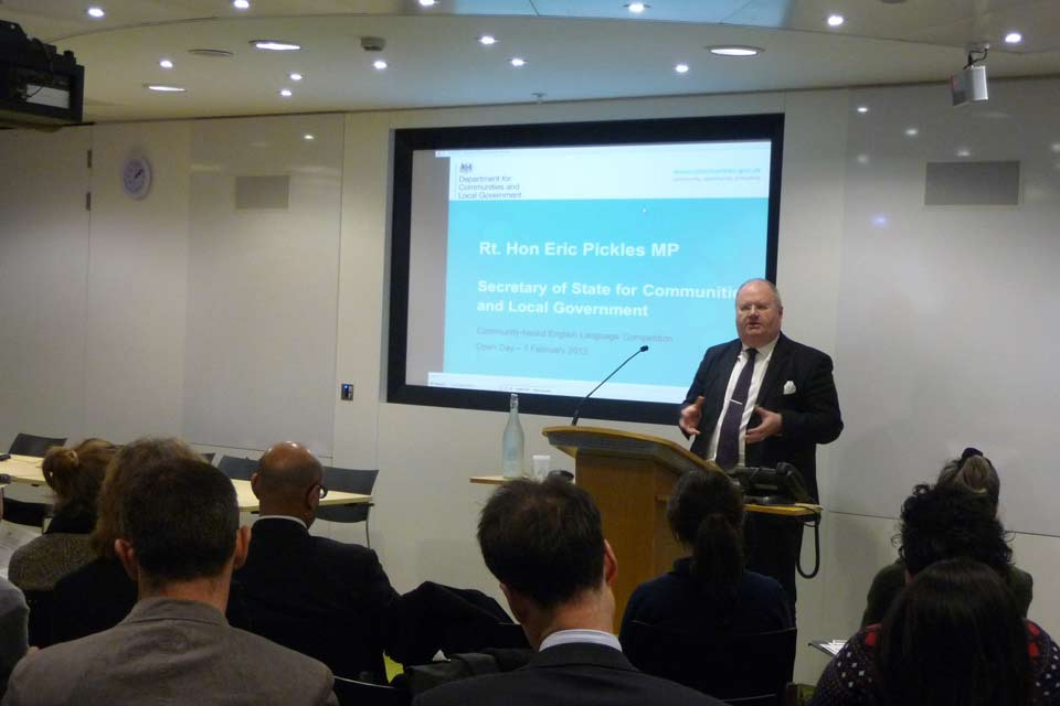 Eric Pickles giving a speech in front of a Powerpoint slide.