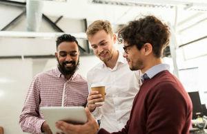Creative team gather around a smart device