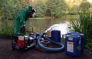 Environment Agency officer dosing Ampthill Reservoir with hydrogen peroxide
