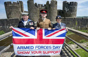Navy, Army and RAF personnel holding Armed Forces Day flag