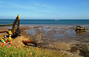 Sand being pumped out of a pipe onto Dawlish Warren beach with construction workers in background