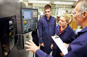 Engineer teaches 2 apprentices how to use a computerised lathe