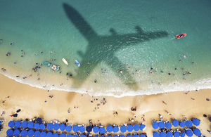 Beach scene with shadow of an aircraft.
