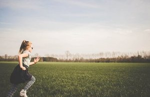 A little girl on the left hand corner of the picture running on a field