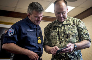 Strike Group Commander Cdre. Andrew Betton, left, looks at photos with Vice Adm. John Christenson, U.S. Military Representative to NATO, aboard the aircraft carrier USS George H.W. Bush.
