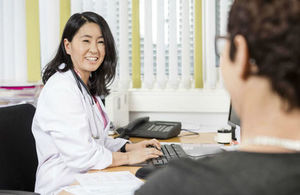 Smiling doctor looks at patient as she types on keyboard
