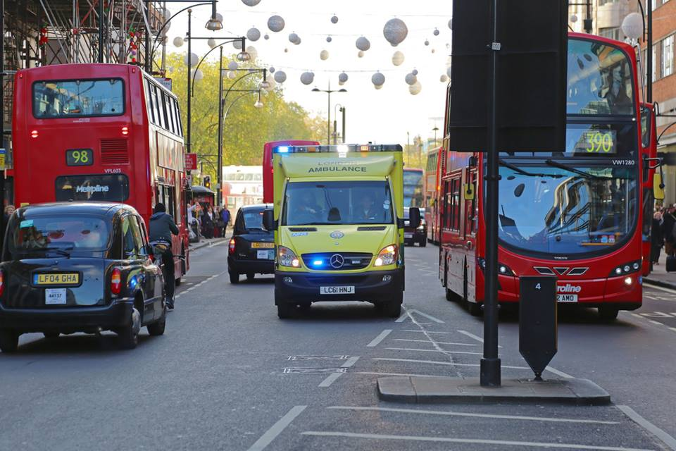 Ambulance on 999 call in London traffic between two red double-decker buses.