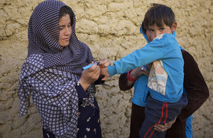 A polio immunisation worker marks the finger of a child with indelible ink as a sign that he has been vaccinated during a national immunisation campaign supported by UK aid. Picture: WHO