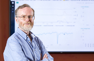 Upside Energy co-founder Graham Oakes standing with arms crossed on he left, with graph on a white board behind him.