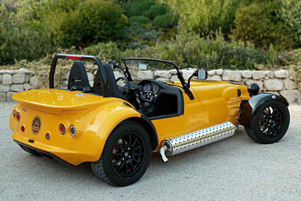 Three-quarter view from the rear of a yellow turbocharged Westfield two-seater sports car.