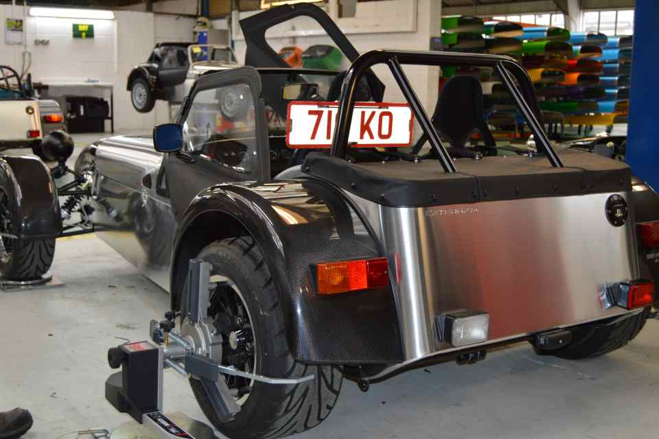 A Caterham test car with monitoring equipment in a company workshop.