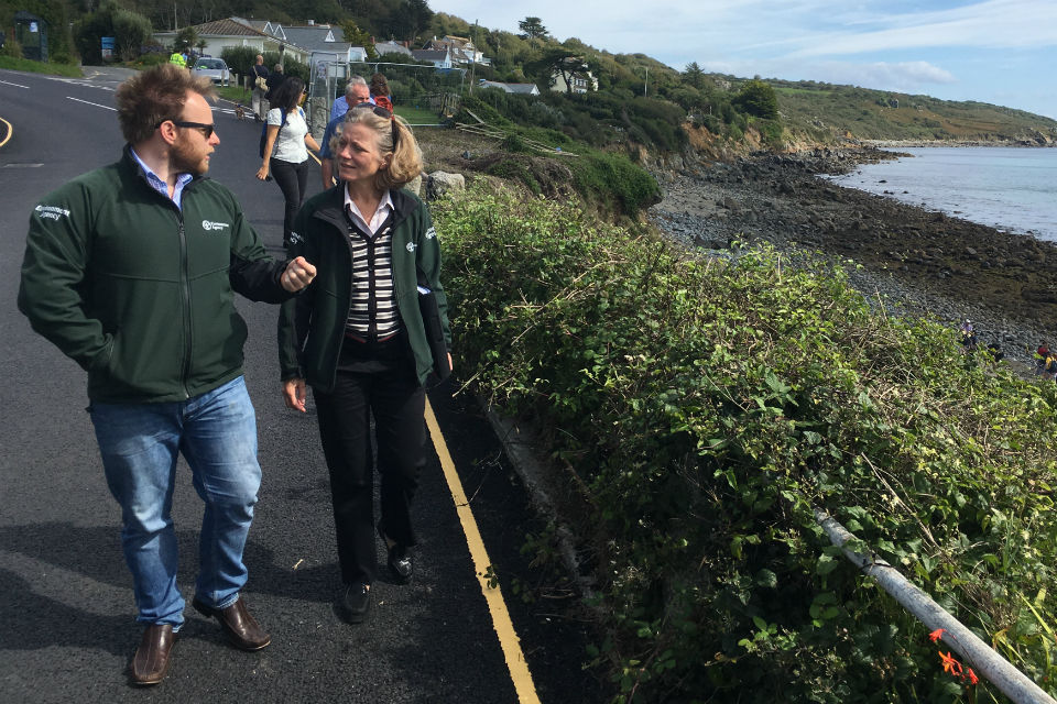 Emma and staff walk along coastal path in Coverack with scaffolding in background