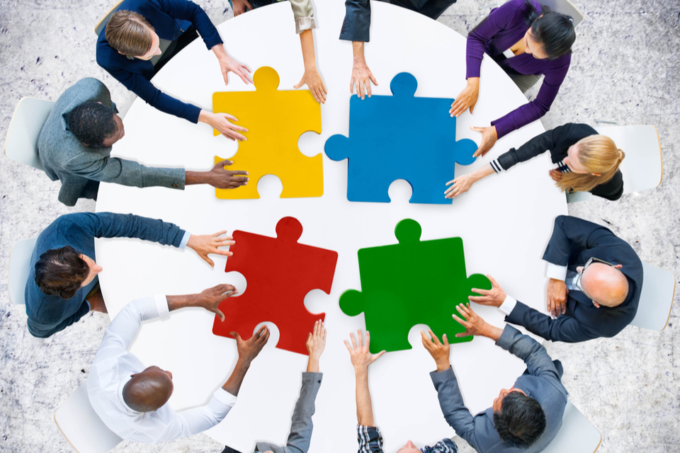 group of people around a round table linking large jigsaw puzzle pieces together