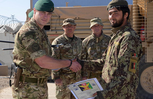 A newly-qualified Afghan explosives expert is congratulated by his British mentor [Picture: Leading Airman (Photographer) Rhys O'Leary, Crown copyright]