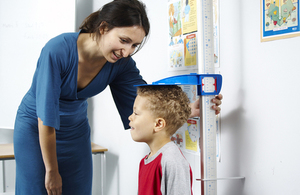 A woman is measuring a young boy's height