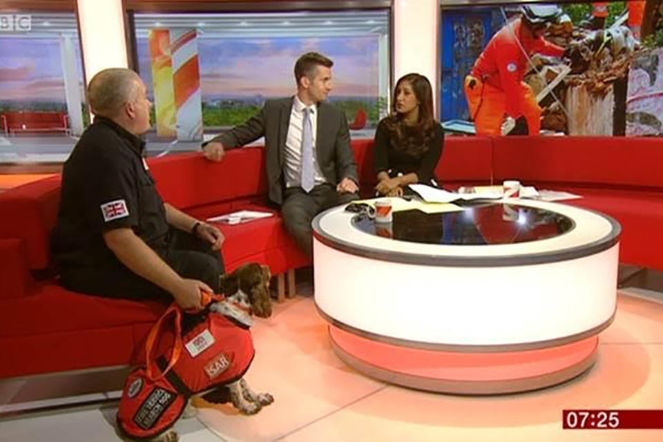 Gary Carroll, a Scottish firefighter and member of the UK's International Search and Rescue Team, pictured on BBC News with his specialist dog, Diesel