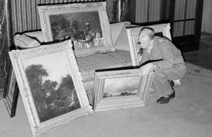 Captain H H Davies of Birkenhead, checks a collection of paintings found in the house of a member of the SS in Hanover in 1945