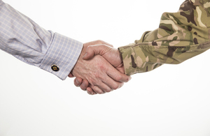 Pictured is a studio shot of a civilian and serviceman shaking hands. Crown copyright.
