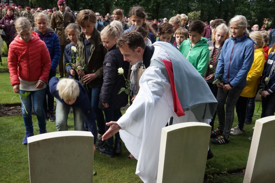 Local school children from Oosterbeek lay flowers on LCpl Loney's grave with the assistance of Reverend Dr Brutus Green, Crown Copyright, All Rights Reserved