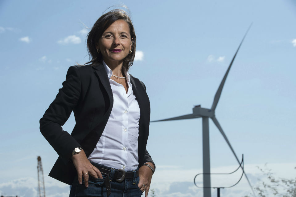 Sabrina Malpede, CEO of ACT Blade, stands in front of a wind turbine