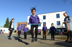 Children playing with hula hoops in front of school watched by teachers against a blue sky.