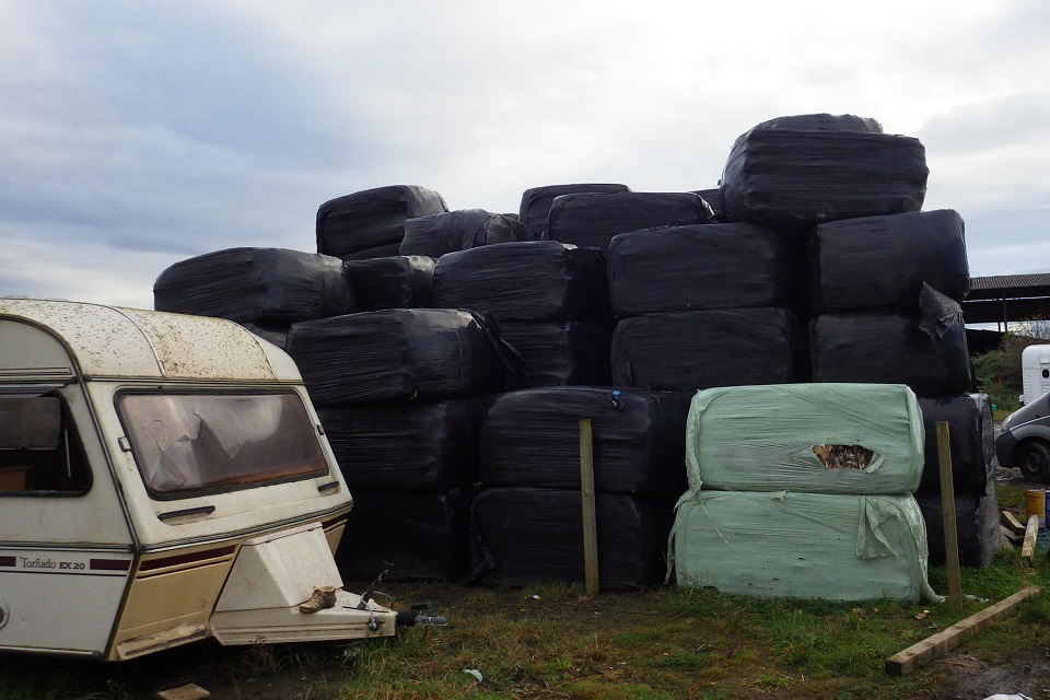 Image shows baled waste dumped on private land