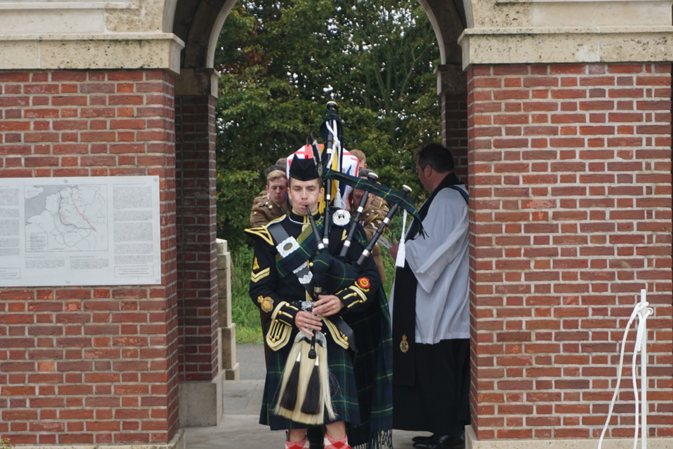 Local piper, Pierre Dervaux, leads the procession into the cemetery - Crown Copyright, All Rights Reserved