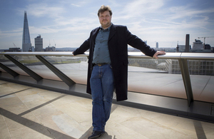 Demand Logic co-founder Joe Short standing on a modern office building terrace with the Shard in the left background.