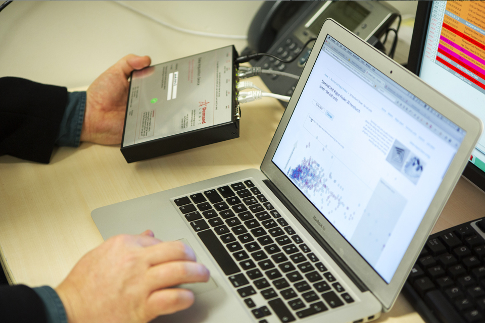 Male hands operating hardware and laptop with Demand Logic visualisation software on screen.