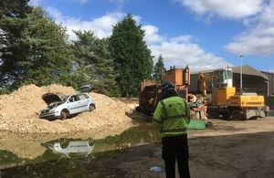 A waste site in the Thames Valley showing an Environment Officer and an old car.