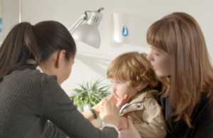 A child sitting on a woman's lap getting a nasal spray