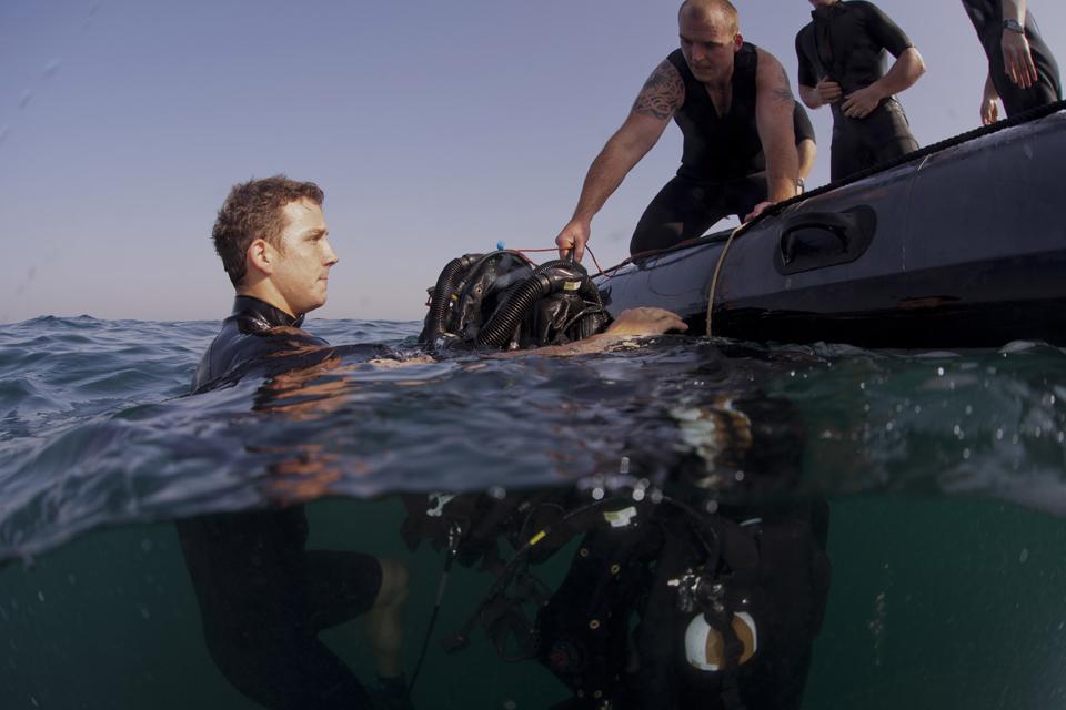 Able Seaman Diver Phil Barham assists Able Seaman Diver Thomas Long