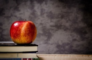 An apple sitting on a small pile of books with a blackboard in the background.