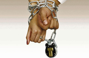 Male and female hands chained and padlocked together